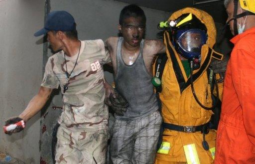 Thai firemen carry an injured man after a fire at the Lee Gardens Hotel in downtown Hat Yai
