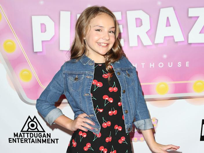 """piper rockelle in 2018 wearing a cherry-patterened dress and jean jacket standing in front of a cut-off sign that reads """"piperazzi"""" on a red carpet"""