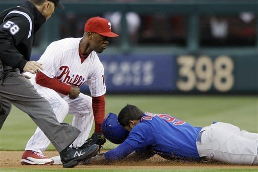 Chicago Cubs' David DeJesus, right, is tagged out at second base by Philadelphia Phillies shortstop Jimmy Rollins while trying to stretch a single in the first inning of a baseball game, Monday, April 30, 2012, in Philadelphia. At left is umpire Dan Iassogna. (AP Photo/Matt Slocum)