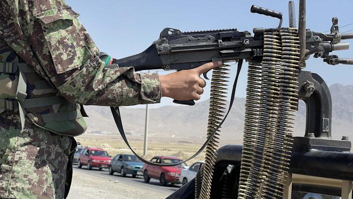 An Afghan soldier stands guard at a checkpoint near the Bagram airfield.