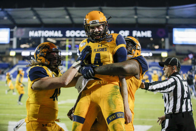 Kent State quarterback Dustin Crum (14) is congratulated by teammates after scoring a touchdown during the second half against Utah State in the Frisco Bowl NCAA college football game Friday, Dec. 20, 2019, in Frisco, Texas. Kent State won 51-41. (AP Photo/Brandon Wade)