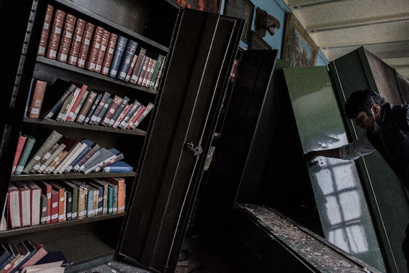 An employee looks at damaged book shelves at the Kaiser Library in Kathmandu on May 7, 2015 (AFP Photo/Philippe Lopez)