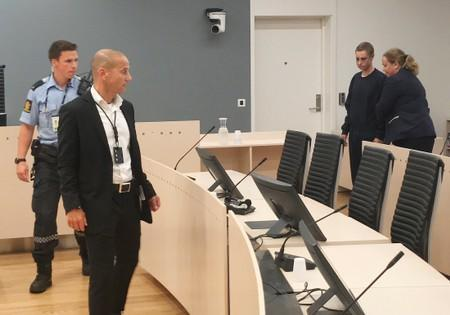 Philip Manshaus, who is suspected of an armed attack at Al-Noor Islamic Centre Mosque and killing his stepsister is escorted into a courtroom in Oslo