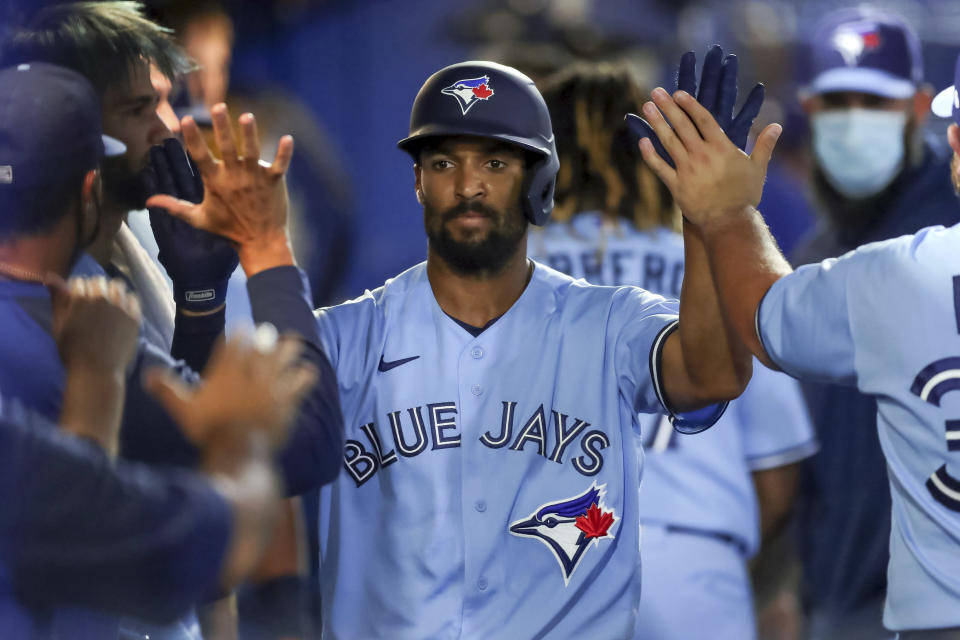 Toronto Blue Jays' Marcus Semien is congratulated in the dugout after his solo home run against the New York Yankees during the fourth inning of a baseball game Tuesday, April 13, 2021, in Dunedin, Fla. (AP Photo/Mike Carlson)