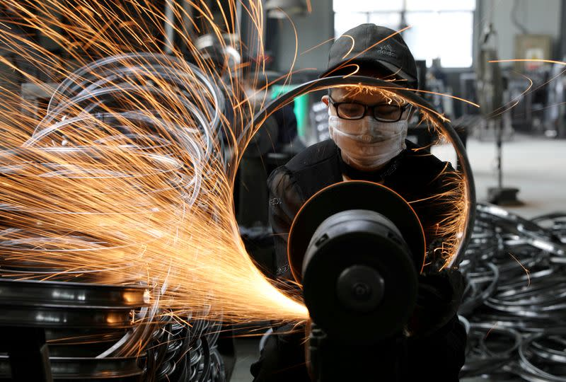 FILE PHOTO: Worker welds a bicycle steel rim at a factory manufacturing sports equipment in Hangzhou, Zhejiang