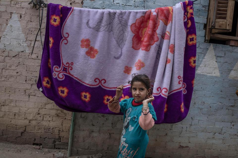 A girl waits outside her home to see if she and her family will get a carton filled with food from non-governmental organization Resala Nour Ala Nour, who are distributing aid to people who have been greatly affected by the coronavirus pandemic, in Cairo, Egypt, Thursday, April 9, 2020. (AP Photo/Nariman El-Mofty)
