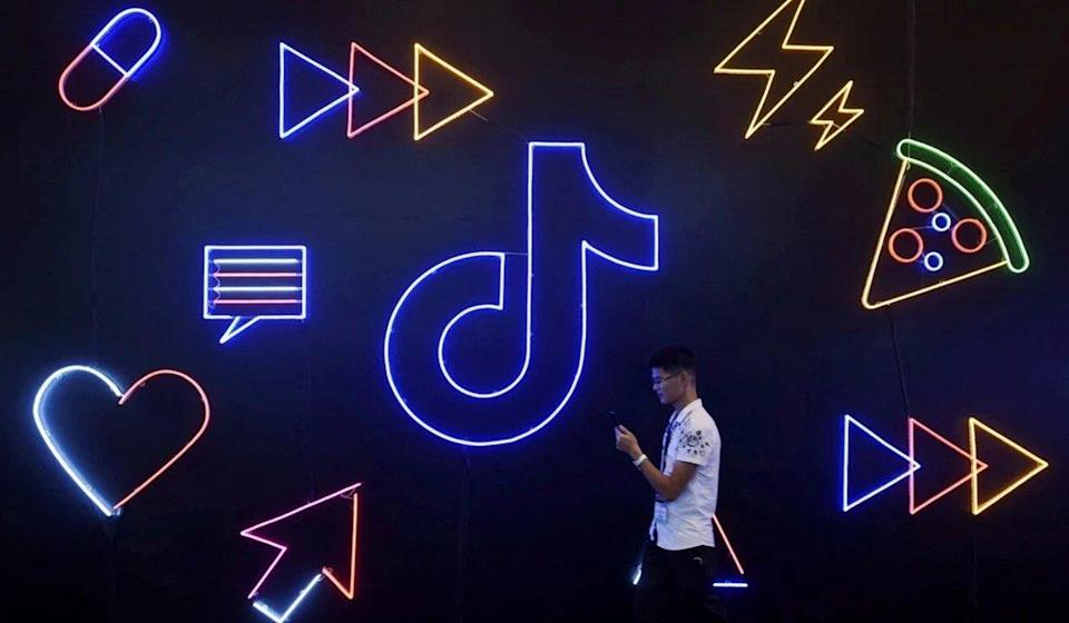 A man holding a phone walks past a sign of TikTok, known locally as Douyin, at the International Artificial Products Expo in Hangzhou, Zhejiang province, China on October 18, 2019. Photo: Reuters