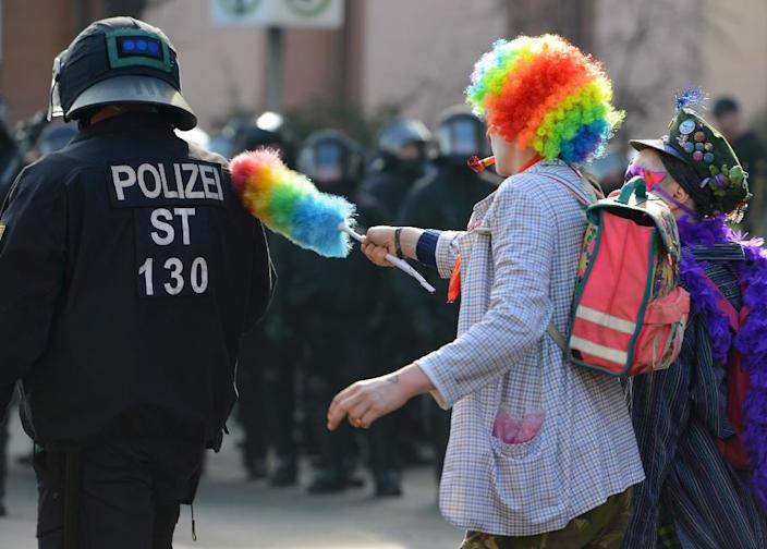 A protester dressed as a clown tries to provoke a police officer as the European Central Bank (ECB) opens its new headquarters in Frankfurt, western Germany, on March 18, 2015 (AFP Photo/Arne Dedert)