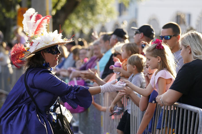 """A woman dressed in period costume hands a trinket to a child during a parade dubbed """"Tardy Gras,"""" to compensate for a cancelled Mardi Gras due to the COVID-19 pandemic, in Mobile, Ala., Friday, May 21, 2021. (AP Photo/Gerald Herbert)"""