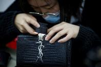 Staff member checks a handbag at the quality control department of the second-hand luxury goods retail platform Plum in Beijing
