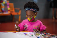 Voylette Bell, 7, writes down and draws positive affirmations on poster board at P.S. 5 Port Morris, a Bronx elementary school, Tuesday, Aug. 17, 2021 in New York. (AP Photo/Brittainy Newman)