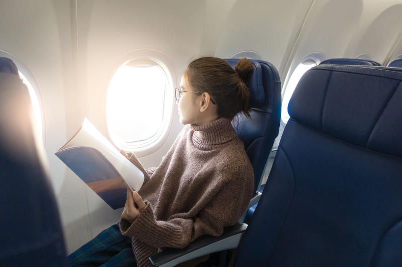 Young Woman Looking Through Window While Sitting With Book In Airplane