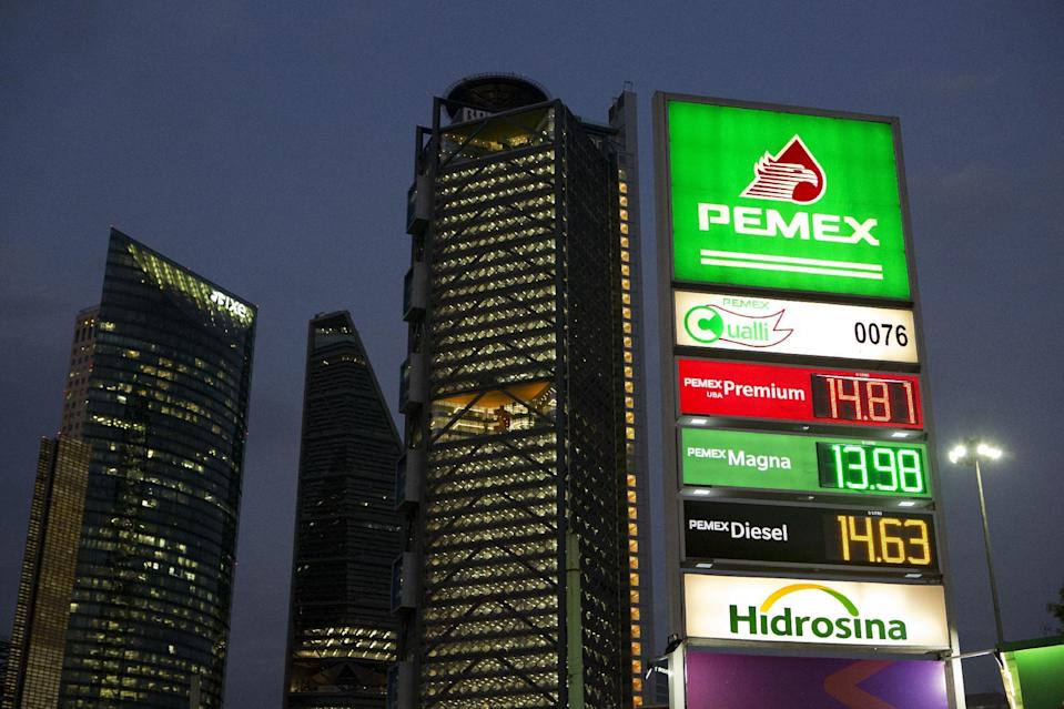 Gas prices per liter are displayed at a station in Mexico City, late Friday, Dec. 30, 2016. Rumors are swirling of gas station owners purportedly hoarding fuel ahead of a price deregulation that takes effect Sunday. Officials say it's time for Mexicans to pay market prices for gasoline and longtime subsidies are not sustainable. (AP Photo/Rebecca Blackwell)