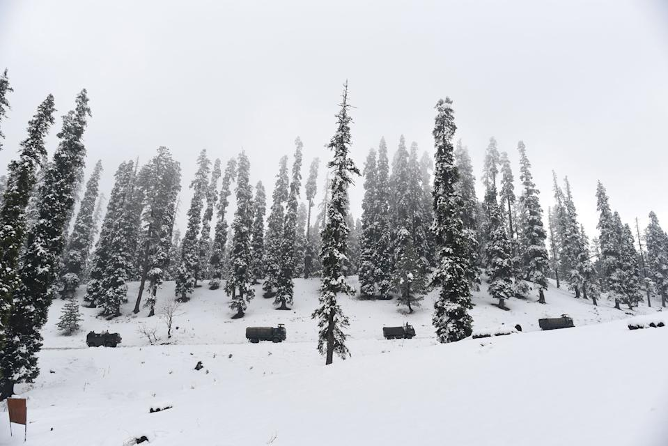 SRINAGAR, INDIA - NOVEMBER 16: Army vehicles make their way across a snow lined Gulmarg road after the seasons first snowfall in the region on November 16, 2020 in Srinagar, India. (Photo by Waseem Andrabi/Hindustan Times via Getty Images)