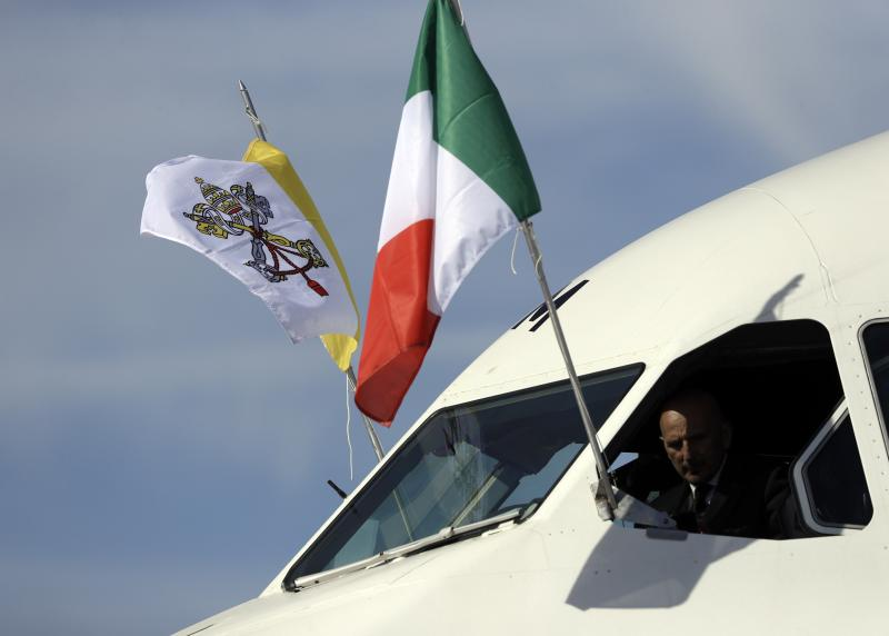 The flags of Italy, right, and the Vatican, fly from the cockpit of the plane carrying Pope Francis to Colombia, as it departs Rome's Leonardo da Vinci international airport in Fiumicino, Wednesday, Sept. 6, 2017. Francis is heading to Colombia on Wednesday for a five-day visit to try to help heal the wounds of Latin America's longest-running conflict, bolstered by a new cease-fire with a holdout rebel group but fully aware of the fragility of the country's peace process. (AP Photo/Gregorio Borgia)