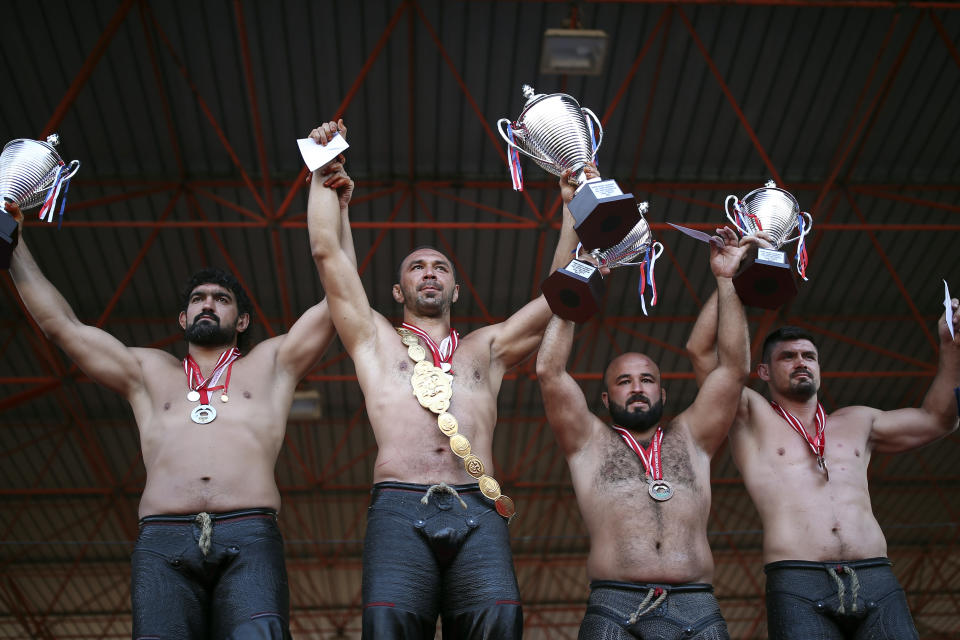 Wrestler Ali Gurbuz, second left, poses for pictures with other top athletes,after winning the final to gain the sport's golden belt in the 660th instalment of the annual Historic Kirkpinar Oil Wrestling championship, in Edirne, northwestern Turkey, Sunday, July 11, 2021.Thousands of Turkish wrestling fans flocked to the country's Greek border province to watch the championship of the sport that dates to the 14th century, after last year's contest was cancelled due to the coronavirus pandemic. The festival, one of the world's oldest wrestling events, was listed as an intangible cultural heritage event by UNESCO in 2010. (AP Photo/Emrah Gurel)