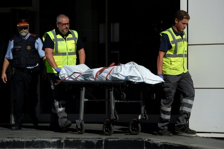 The body of a man who tried to attack a police station is carried out of the premises in Cornella near the northeastern Spanish city of Barcelona