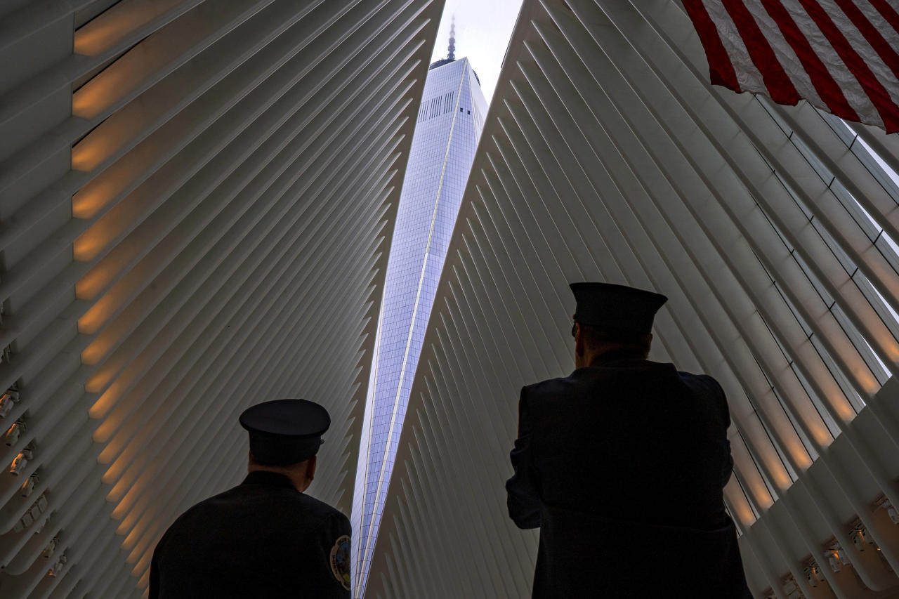 Two members of the New York City fire department look towards One World Trade Center through an opeining in the ceiling of the Oculus, part of the World Trade Center complex in New York, Tuesday, Sept. 11, 2018, the anniversary of 9/11 terrorist attacks. The transit hall ceiling window was opened just before 10:28 a.m., marking the moment that the North Tower of the World Trade Center collapsed on September 11, 2001. (AP Photo/Craig Ruttle)