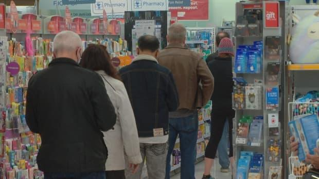 People wait in line to book an appointment for the Oxford-AstraZeneca vaccine at a Shoppers Drug Mart in Vancouver on March 31, 2021.