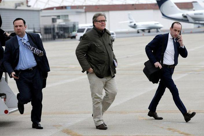 Stephen Bannon, center, walks from President Trump's plane upon their arrival in Indianapolis, Ind. (Photo: Mike Segar/Reuters)