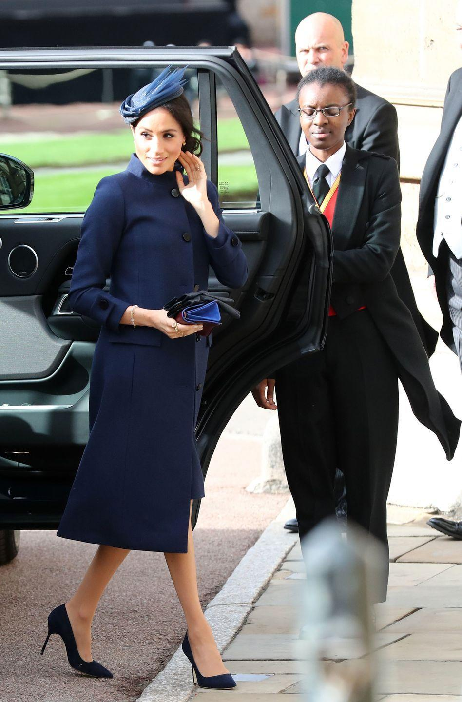 """<p><a href=""""https://www.townandcountrymag.com/society/tradition/a23552769/meghan-markle-givenchy-dress-princess-eugenie-wedding-photos/"""" rel=""""nofollow noopener"""" target=""""_blank"""" data-ylk=""""slk:Meghan Markle"""" class=""""link rapid-noclick-resp"""">Meghan Markle</a> wore a sleek navy blue dress and coat designed by Givenchy while attending Princess Eugenie's wedding. She finished her look with matching heels and a fascinator by Noel Stewart.</p>"""