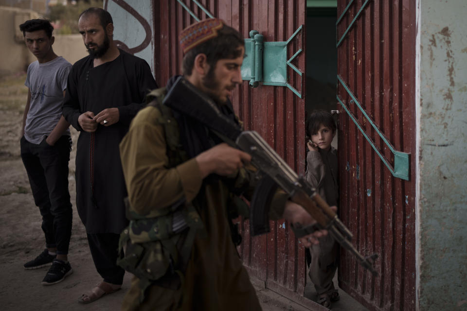 An afghan boy watches as Taliban fighters search for a man accused of stabbing, in Kabul, Afghanistan, Sunday, Sept. 12, 2021.It is a symbol of the moment of transition they find themselves in: Once warriors embedded in Afghanistan's rugged mountains, now the Taliban are an urban police force. (AP Photo/Felipe Dana)