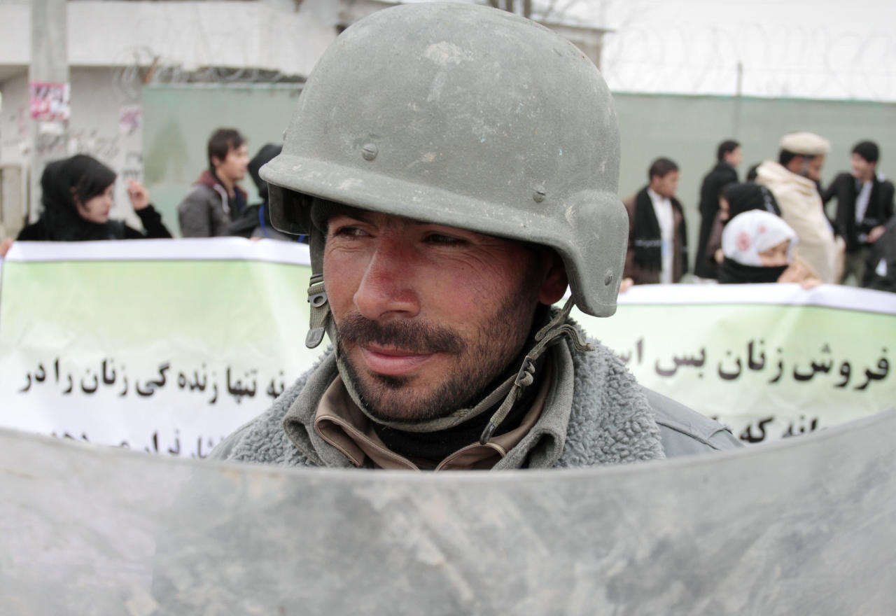 An Afghan riot police officer stands guard during a march calling for end of violence against women in Kabul, Afghanistan, Thursday, Feb. 14, 2013. Dozens of Afghan activists have marked Valentine's Day by marching in Kabul to denounce violence against women. Concern has risen after rights organizations last year found that Afghan women are frequently victims of violence — despite a law against it and increased prosecution of abusers. (AP Photo/Musadeq Sadeq)