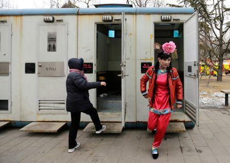 A male folk artist (R) dressed as a traditional Chinese woman walks out of a mobile toilet ahead of a performance at a Spring Festival Temple Fair on the fifth day of the Chinese Lunar New Year at Longtan Park in Beijing, China February 14, 2013. REUTERS/Jason Lee/File Photo