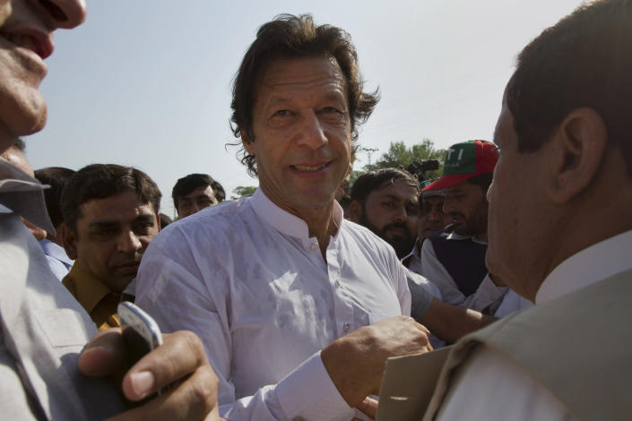 "Pakistan's ex-cricket star-turned-politician Imran Khan, center, is surrounded by his supporters as he arrives to lead what organizers are calling the ""peace march,"" in Islamabad, Pakistan, Saturday, Oct. 6, 2012. Hundreds of Pakistanis, joined by dozens of American activists, set off Saturday on a motorcade ""march"" to protest against U.S. drone strikes, hoping to reach a militant-riddled Afghan border region that has been the focus of many such attacks. (AP Photo)"