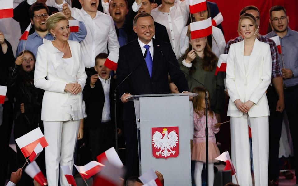 Poland's Andrezj Duda speaks to supporters, flanked by his wife and daughter - Bloomberg