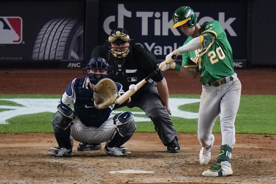 Oakland Athletics' Mark Canha hits a single during the seventh inning of the team's baseball game against the New York Yankees on Friday, June 18, 2021, in New York. The Athletics won 5-3. (AP Photo/Frank Franklin II)