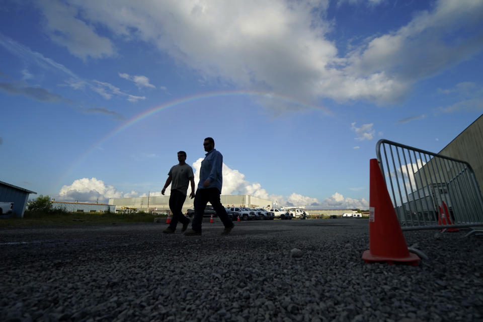 """Josiah Goodman, left, and Austin Fleetwood, of Berryville, Ark. workers for Carroll Electric Cooperative Corporation, walk with a rainbow above them, through a tent city for electrical workers in Amelia, La., Thursday, Sept. 16, 2021. When Hurricane Ida was brewing in the Gulf of Mexico, the grass was chest high and the warehouse empty at this lot in southeastern Louisiana. Within days, electric officials transformed it into a bustling """"tent city"""" with enormous, air-conditioned tents for workers, a gravel parking lot for bucket trucks and a station to resupply crews restoring power to the region. (AP Photo/Gerald Herbert)"""