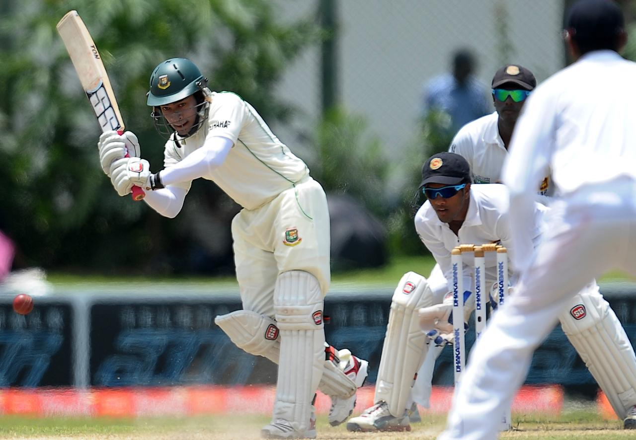 Bangladeshi captain Mushfiqur Rahim (L) is watched by Sri Lankan wicketkeeper Dinesh Chandimal as he plays a shot during the third day of the opening Test match between Sri Lanka and Bangladesh at the Galle International Cricket Stadium in Galle on March 10, 2013.   AFP PHOTO/ LAKRUWAN WANNIARACHCHI        (Photo credit should read LAKRUWAN WANNIARACHCHI/AFP/Getty Images)