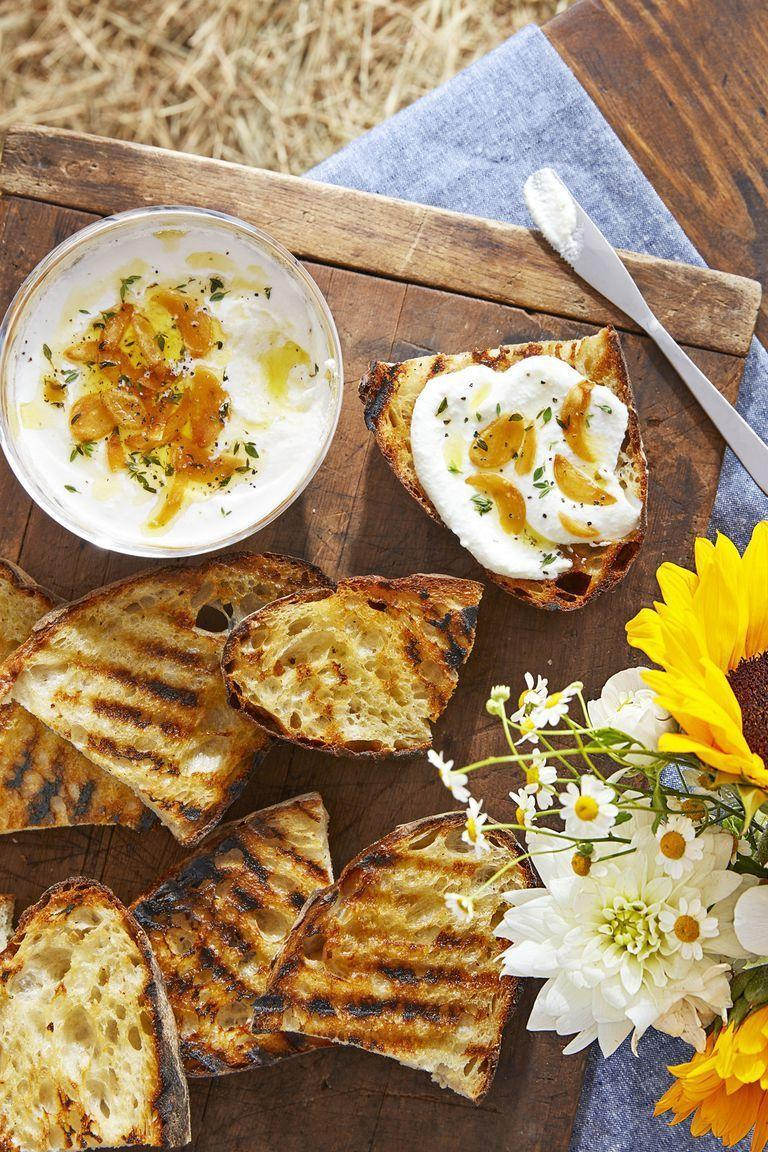 """<p>This deliciously simple appetizer is finished off with sautéed garlic and a drizzle of olive oil.</p><p><strong><a href=""""https://www.countryliving.com/food-drinks/a22665799/whipped-ricotta-and-grilled-bread-recipe/"""" rel=""""nofollow noopener"""" target=""""_blank"""" data-ylk=""""slk:Get the recipe"""" class=""""link rapid-noclick-resp"""">Get the recipe</a>.</strong></p>"""