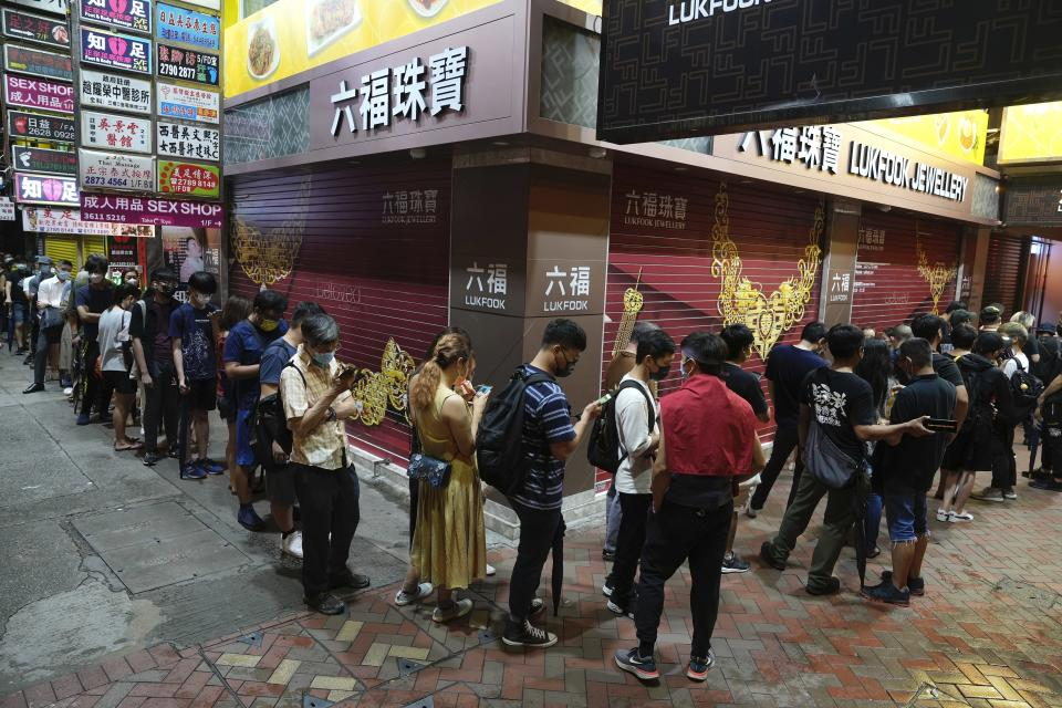 People queue up near a newspaper booth to buy last copy of Apple Daily in Hong Kong, early Thursday, June 24, 2021. Hong Kong's pro-democracy Apple Daily newspaper will stop publishing Thursday, following last week's arrest of five editors and executives and the freezing of $2.3 million in assets under the city's year-old national security law. (AP Photo/Vincent Yu)