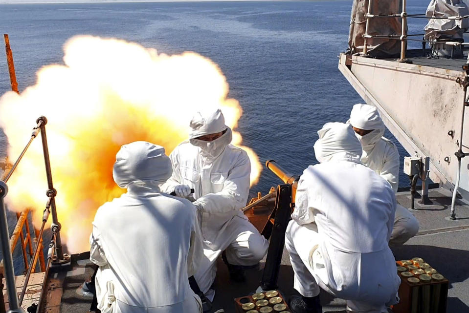This handout photo provided by the Ministry of Defense shows crew members of the HMS Montrose firing a 41-round gun salute to to mark the death of the Duke of Edinburgh, in Duqm, Oman. Britain's Prince Philip, the irascible and tough-minded husband of Queen Elizabeth II who spent more than seven decades supporting his wife in a role that mostly defined his life, died on Friday. (Jay Allen/Ministry of Defense via AP)
