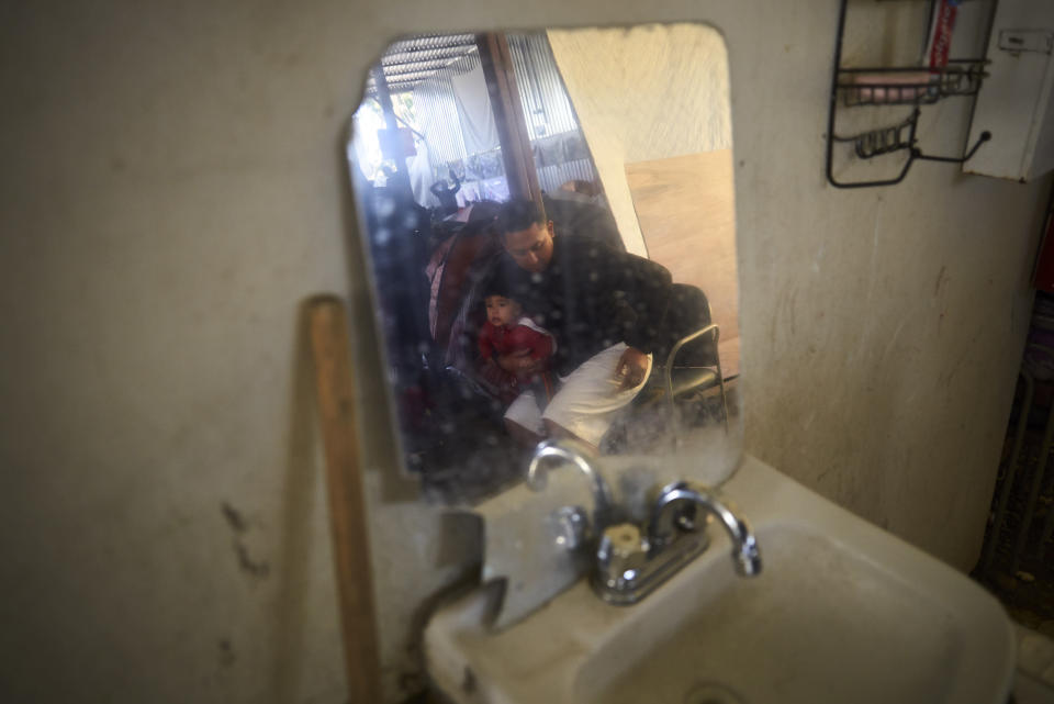 "In this March 5, 2019, image, Juan Carlos Perla holds his 10-month-old son, Joshua, reflected in a mirror inside a shelter for migrants in Tijuana, Mexico. ""Our fear is that we lose our case and get deported"" to El Salvador, Perla said. ""That's suicide for me, my wife and my children."" (AP Photo/Gregory Bull)"