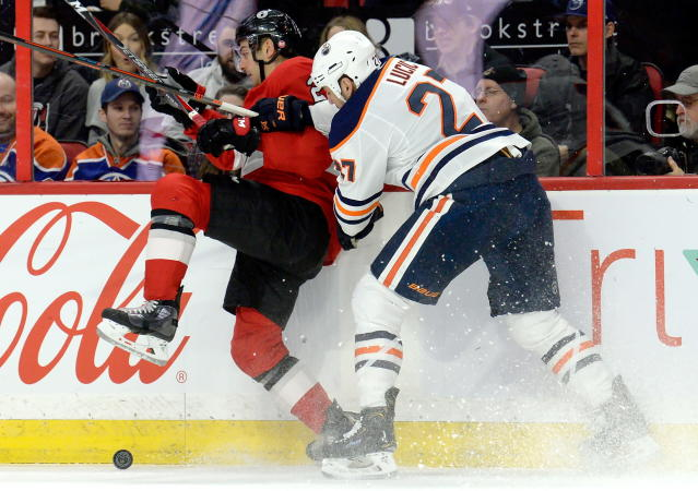 Edmonton Oilers' Milan Lucic (27) collides with Ottawa Senators' Dylan DeMelo during the first period of an NHL hockey game Thursday, Feb. 28, 2019, in Ottawa, Ontario. (Adrian Wyld/The Canadian Press via AP)