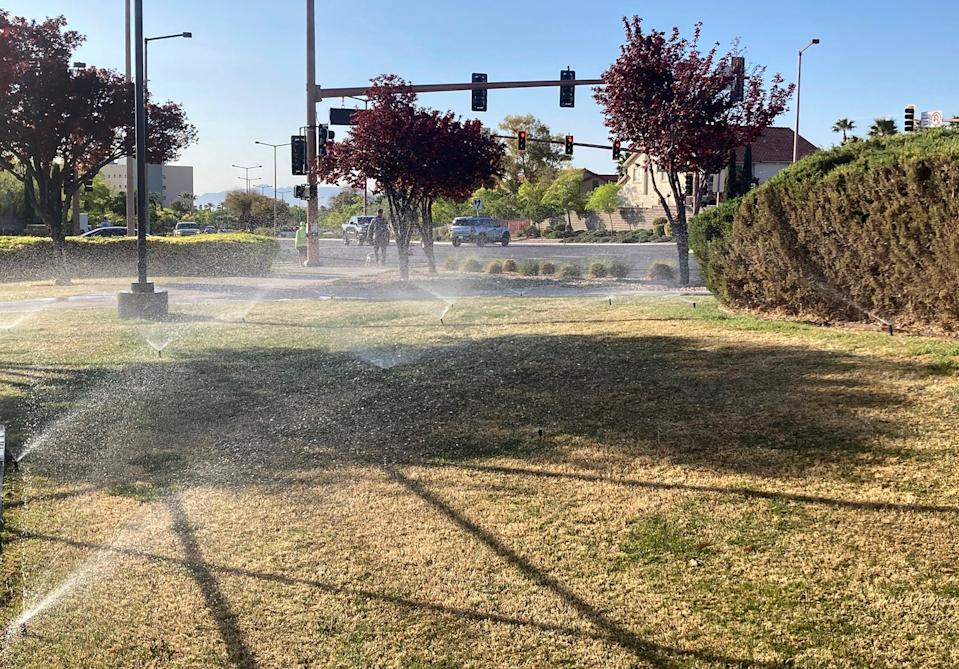 <p>Sprinklers water grass near a street corner on 9 April, 2021, in the Summerlin neighborhood of Las Vegas</p> (AP)
