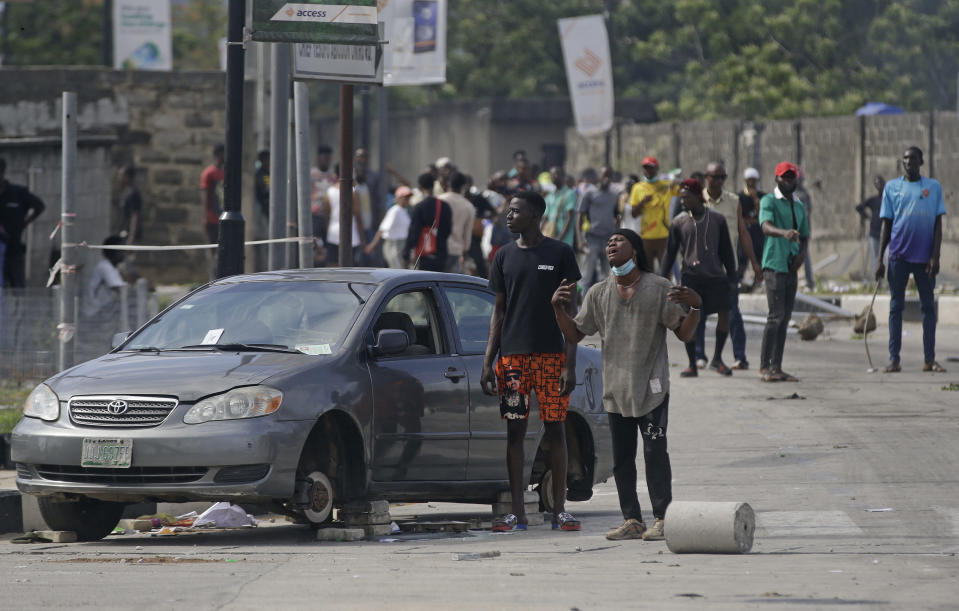 People protest against alleged police brutality near to the Lekki toll gate in Lagos, Nigeria, Wednesday Oct. 21, 2020. After 13 days of protests against alleged police brutality, authorities have imposed a 24-hour curfew in Lagos, Nigeria's largest city, as moves are made to stop growing violence. ( AP Photo/Sunday Alamba)
