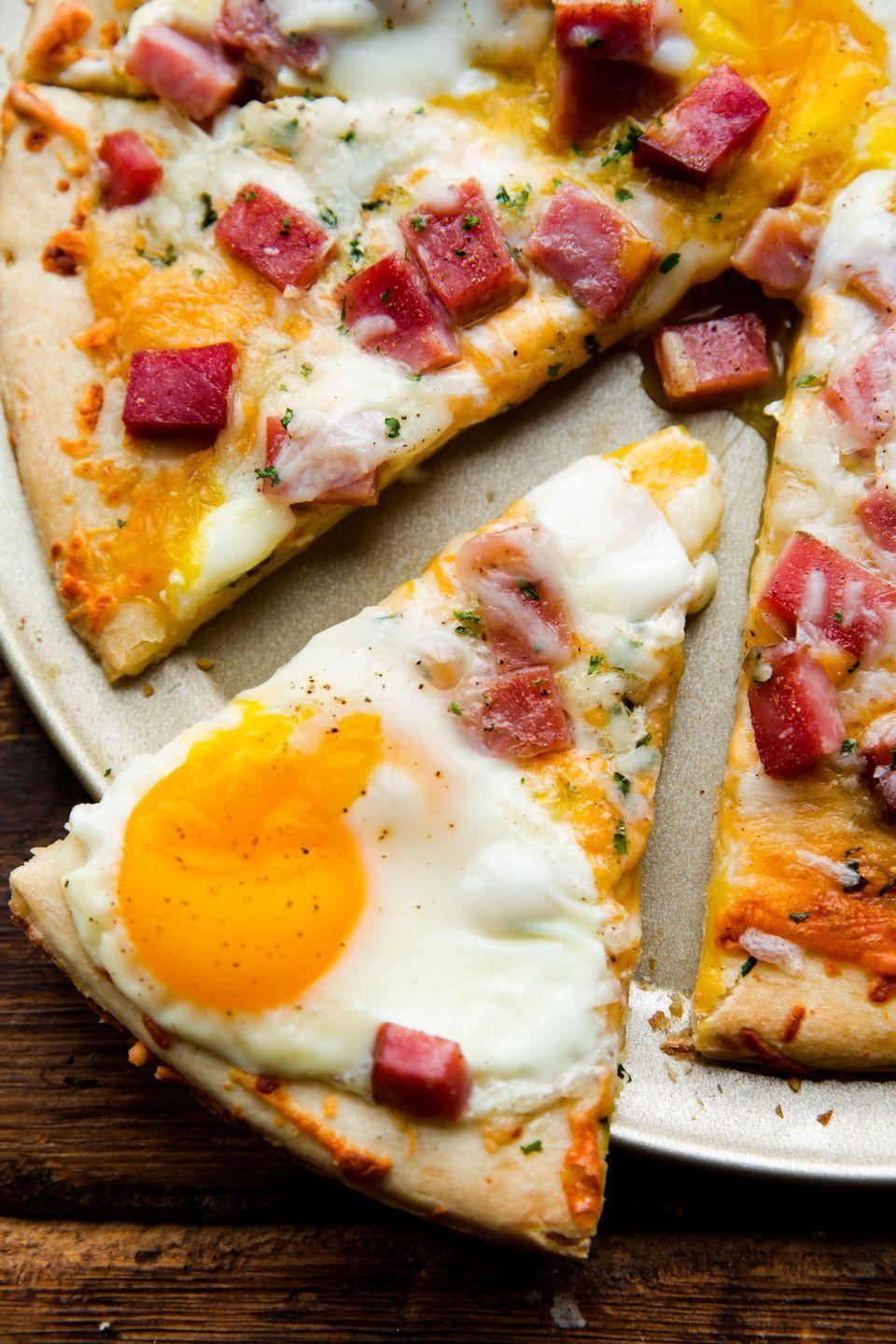 "<p>If you're short on time and crave breakfast for dinner (wait, isn't that every night?) this super simple pizza has your name all over it. You can really use any cheese you have, but don't forget those mouthwatering eggs on top! </p><p>Get the recipe from <a href=""https://www.delish.com/cooking/recipe-ideas/recipes/a52788/ham-egg-cheese-breakfast-pizza-recipe/"" rel=""nofollow noopener"" target=""_blank"" data-ylk=""slk:Delish"" class=""link rapid-noclick-resp"">Delish</a>.</p>"
