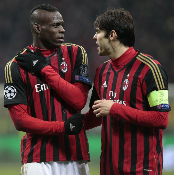 AC Milan's forward Mario Balotelli, left, is encouraged by team's captain Ricardo Kaka after he injured himself during a round of 16th Champions League soccer match between AC Milan and Atletico Madrid at the San Siro stadium in Milan, Italy, Wednesday, Feb. 19, 2014. (AP Photo/Emilio Andreoli)