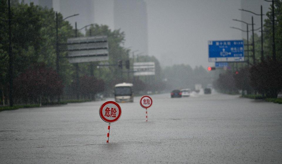 Danger signs are seen on a waterlogged road in Zhengzhou, on Tuesday. Photo: Xinhua