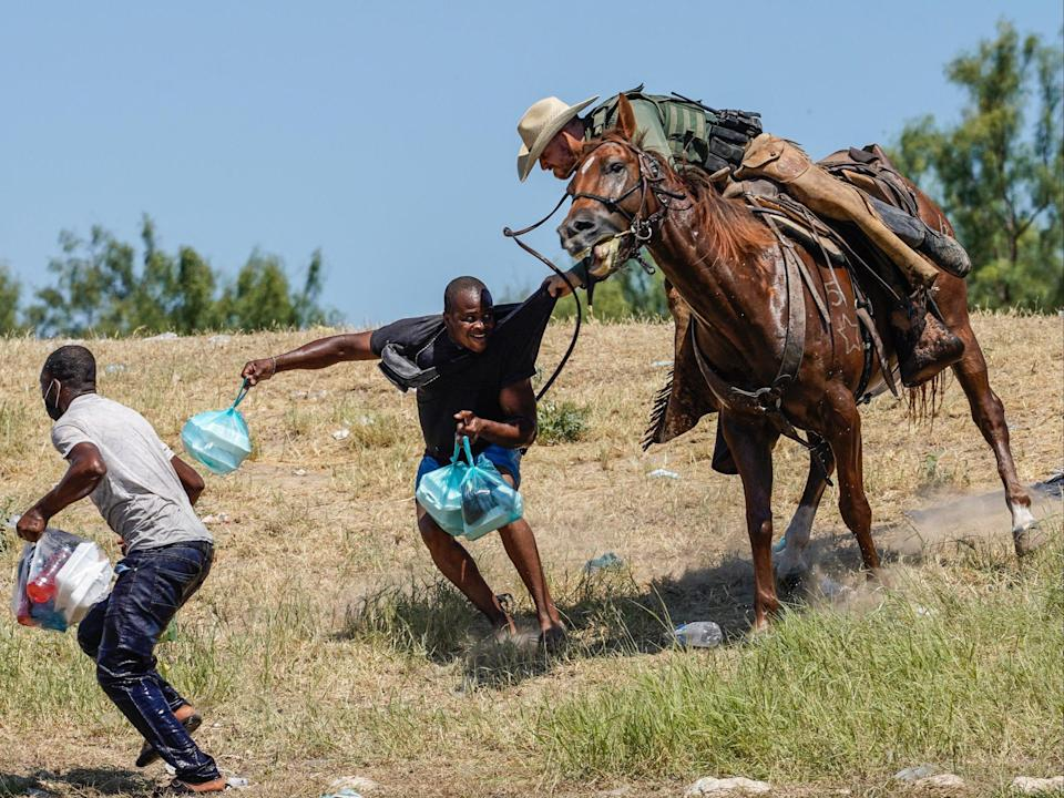 A United States Border Patrol agent on horseback tries to stop a Haitian migrant from entering an encampment on the banks of the Rio Grande near the Acuna Del Rio International Bridge in Del Rio, Texas, on 19 September (AFP via Getty Images)