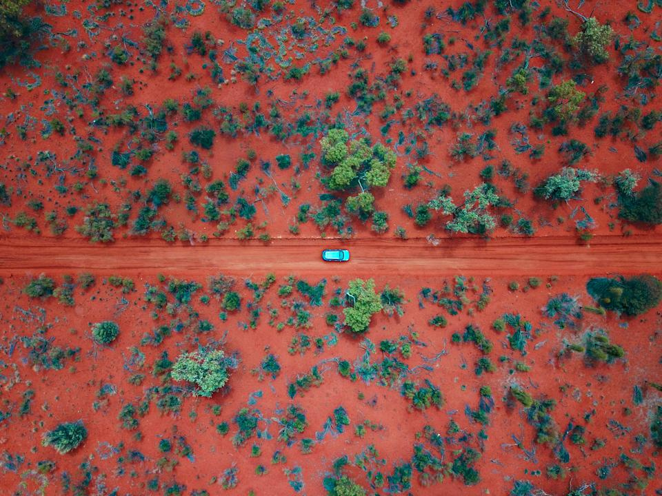 An Aerial shot of a car driving on the red dirt roads in the Australian Outback