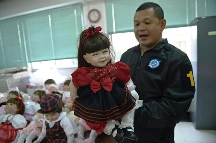 """A Thai policeman shows a """"luuk thep"""" (child angel) doll in Bangkok on January 26, 2016 after more than a hundred of them were seized in raids (AFP Photo/)"""