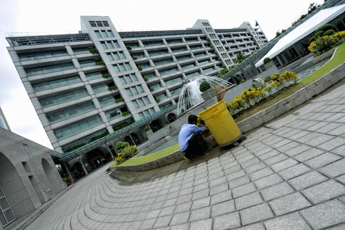 File Photo: A worker cleans the ground of the Asian Development Bank (ADB) headquarters in Manila. (Photo: JAY DIRECTO/AFP via Getty Images)
