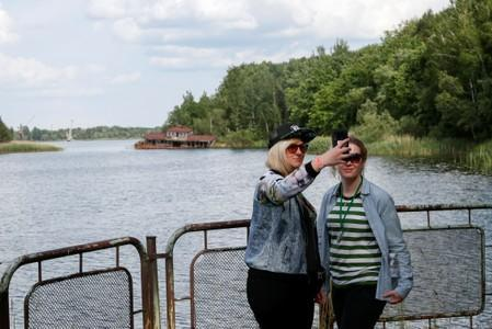 Visitors take a selfie at a river port of the abandoned city of Pripyat, near the Chernobyl nuclear power plant