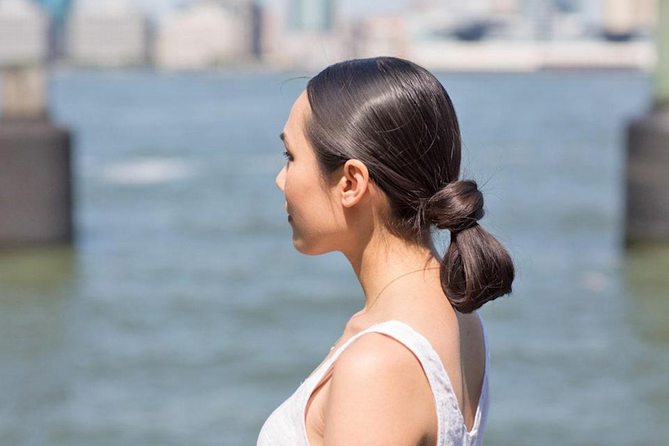 If a low bun is your go-to style, try this variation on it instead. It's just as sleek but a little more interesting. The trick? When you go to pull your ponytail through your holder, keep half of it tucked in, then loop the other half around the elastic. Secure it in place underneath so no bobby pins show.