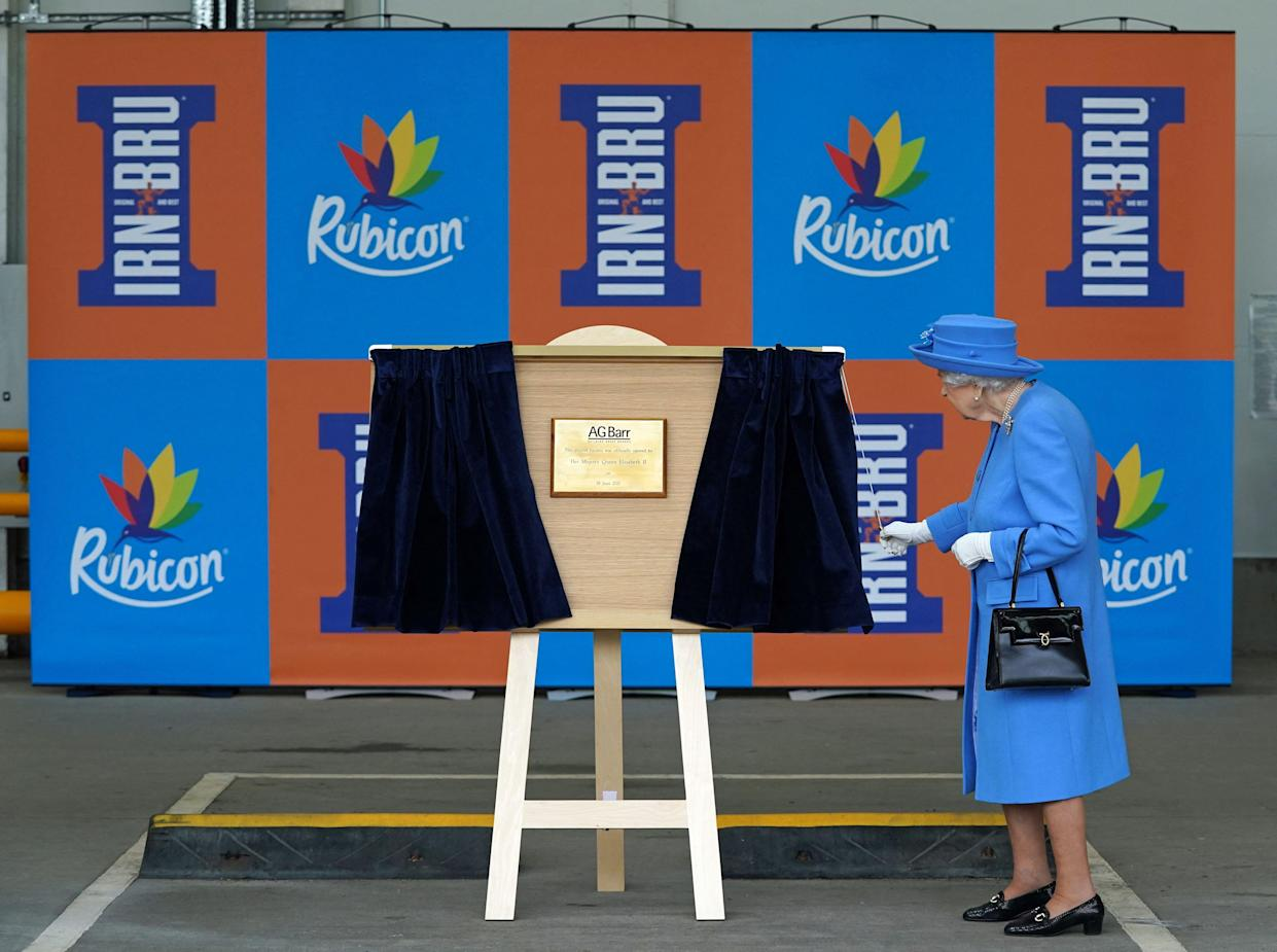 Britain's Queen Elizabeth II unveils a plaque during a visit to AG Barr's factory in Cumbernauld, east of Glasgow, where the Irn-Bru drink is manufactured on June 28, 2021. - The Queen is in Scotland for Royal Week where she will be undertaking a range of engagements celebrating community, innovation and history. (Photo by Andrew Milligan / POOL / AFP) (Photo by ANDREW MILLIGAN/POOL/AFP via Getty Images)